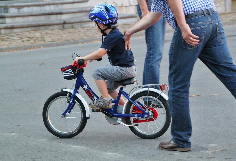 rodiče učí dítě jezdit na kole