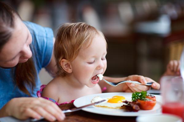 dítě sedí za stolem a maminka ho krmí příborem