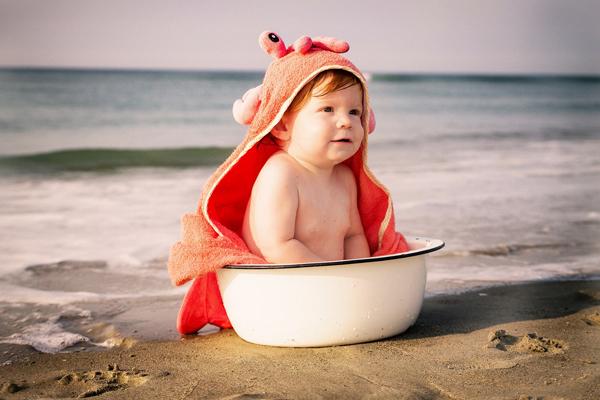 Jak naučit dítě chodit na nočník? Dítě sedí v lavoru, který je na pláži.