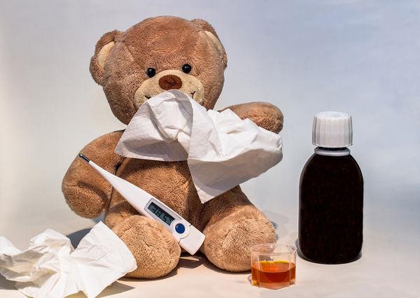 Plyšový medvěd s kapesníkem, teploměrem a léky.