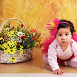 Lezoucí holčička po kolenou a vedle ní koš s květinami.