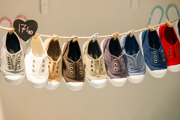 Jak naučit dítě chodit? Spousta malých botiček se suší na šňůře.