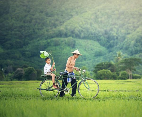 Děti jedou na kole přes louku