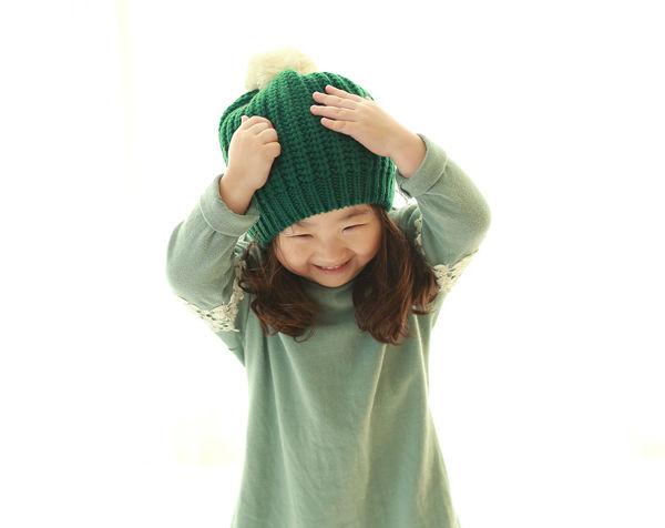 Holčička si obléká čepici a směje se u toho