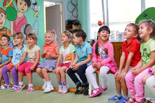 Jak naučit dítě oblékat? Děti sedí ve školce na lavici a povídají si.