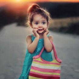 Jak naučit dítě oblékat? Holčička s kabelkou se usmívá