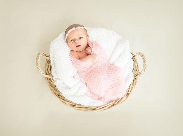 Jak naučit dítě usínat samo? Miminko leží v košíku a zavinovačce