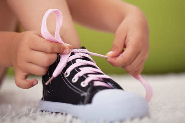Jak naučit dítě zavazovat tkaničky? Černá kotníčková dětská obuv s růžovými tkaničkami. Dítě zavazuje botu.