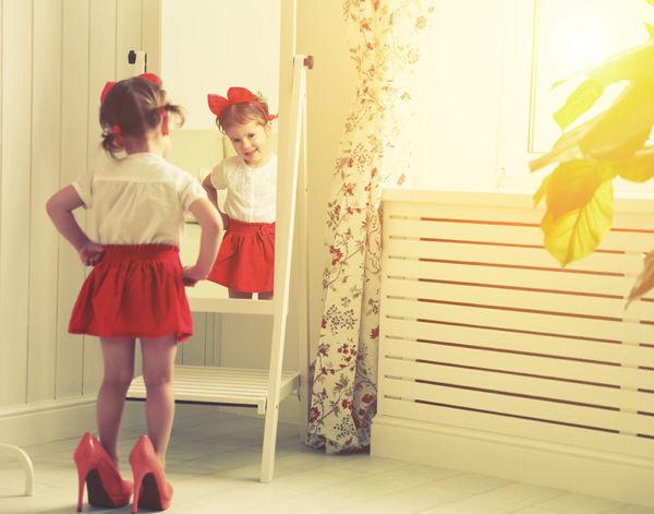 Holčička stojí v červených lodičkách na podpatku před zrcadlem.
