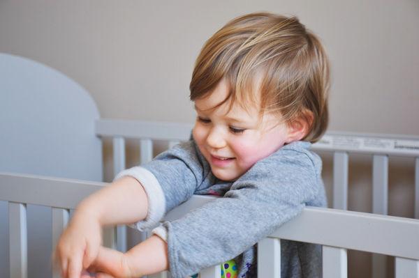 Dítě stojící v postýlce.