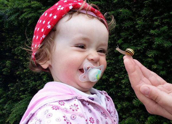 Jak naučit dítě od dudlíku? Smějící se dítě s dudlíkem v puse.