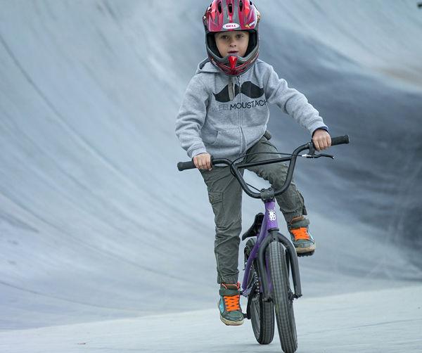 Dítě jede na kole a za ním je vlna.