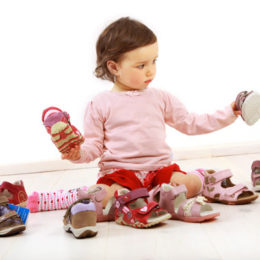 Holčička sedí mezi botami a prohlíží si je.