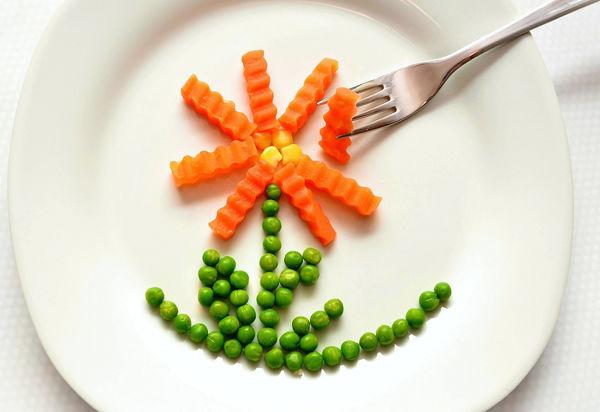 Jak naučit dítě zdravě jíst? Fotografie zeleniny na talíři ve tvaru květiny.