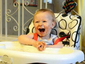 Jak naučit dítě jíst lžičkou, smějící se dítě u stolečku, špinavé od jídla