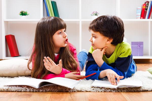 Fotografie holčička s chlapcem si na zemi v leže povídají, Jak naučit dítě říkat r