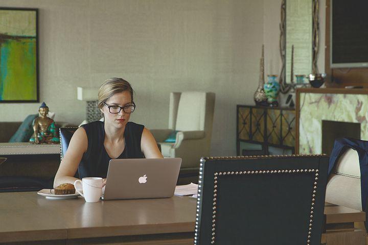 Fotografie ženy sedící u stolu a pracující na PC