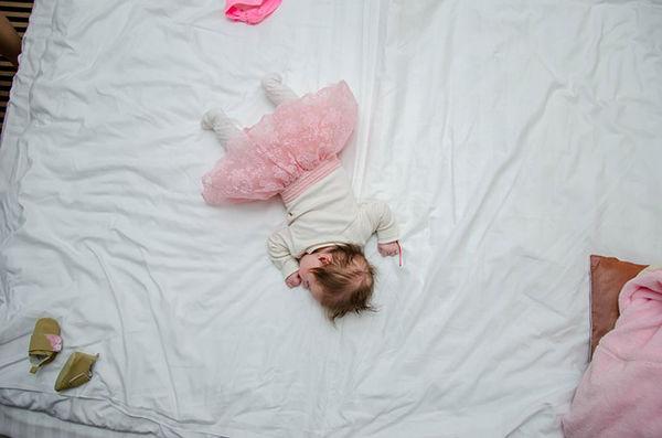 Fotografie miminka jak spí ve velké posteli
