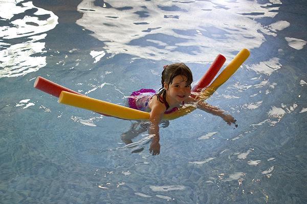 Fotografie dítěte jak plave s plovacími deskami v bazénu. jak učit dítě plavat