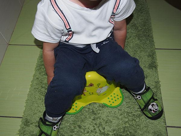 Fotografie chlapečka sedícího na nočníku