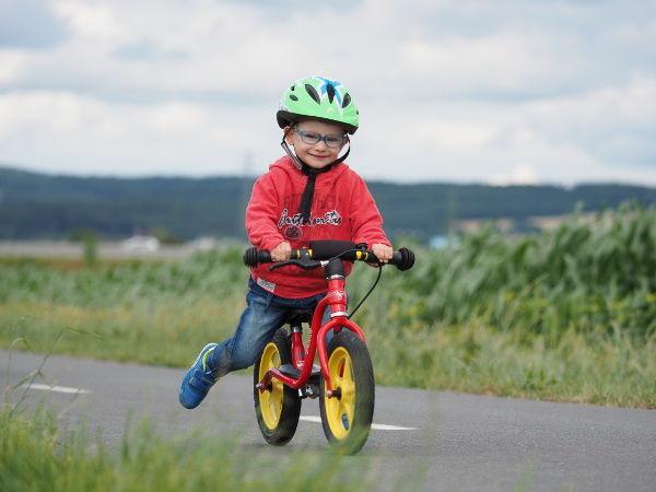 dítě jede po cyklostezce na červeném kolo odrážedle puky - foto z článku: jak naučit dítě na odrážedle