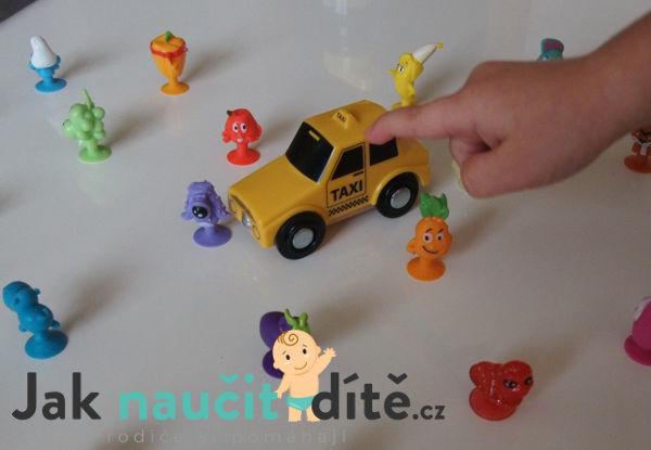 Stikeez přilepené na stole a dětská ruka mezi nimi jezdí autíčkem